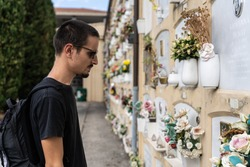 Stock photo of a Boy dressed in black and with a suitcase and sunglasses, looking at a tomb in a cemetery in Bologna, Italy. Travel concept