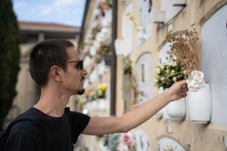 Stock photo of a boy dressed in black and with a suitcase and sunglasses, touching the flowers of a tomb in a cemetery in Bologna, Italy. Travel concept