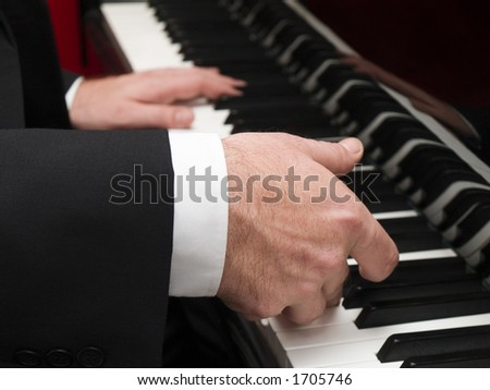 Stock photo of a closeup of a man\'s hands playing a piano.
