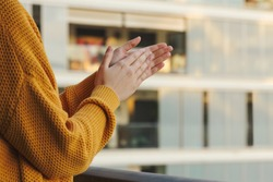 Stock photo of a girl's hands applauding from her balcony to support those fighting coronavirus