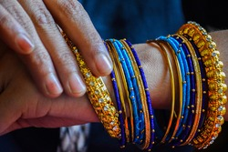 Stock photo of a hand of Indian women wearing colorful bangles with gold Indian design bracelet, picture captured at the time of Indian wedding season at Bangalore Karnataka India.