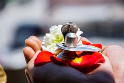 Stock photo of a man holding and worshiping silver shivlinga which is icon of lord shiva on the occasion of mahashivratri , flowers around the shivlinga in bright sunlight at Bangalore city karnataka