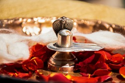 Stock photo of a silver shivlinga which is icon of lord shiva snake above shivlinga, being worshiped flowers and cotton garland on occasion of Indian festival mahashivratri or shivratriq