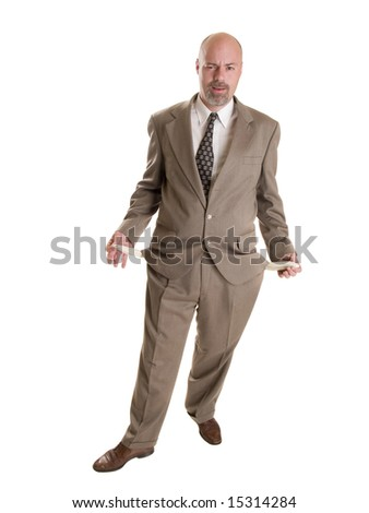Stock photo of a well dressed broke businessman holding his empty pockets