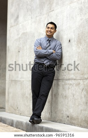 Stock photo of a well dressed Hispanic businessman leaning against a concrete wall and looking up.