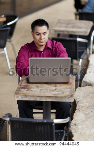 Stock photo of a well dressed Hispanic businessman looking down at a laptop while telecommuting from an internet cafe.