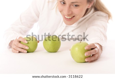 Stock photo of a young happy woman with green apples