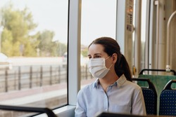 Stock photo of a young woman wearing a face mask traveling by tram. She is looking out the window. New normal concept