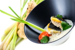 Stock photo of deep dish with fish with scum and vegetables to decorate