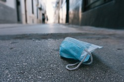 Stock photo of disposable face mask thrown in the floor. Pollution concept.