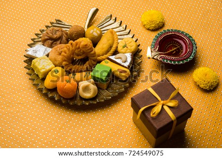 stock photo of Indian sweet or mithai and oil lamp or diya with gift box and flowers on decorative or colourful background, selective focus\n