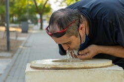 Stock photo of middle age man with face mask drinking water from a fountain.