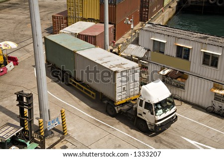 Stock photo of shipping containers on semi-trailer leaving a container terminal on Victoria Harbour Hong Kong, stacked containers in background.