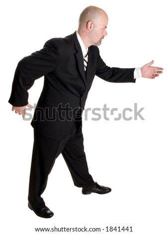 Stock photo of the side view of a well dressed businessman holding his hand out in a gesture as if pulling a rope or asking a woman to dance.  Full length, isolated white.