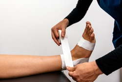 Stock photo of unrecognized worker in physiotherapy clinic wrapping patient's feet with bandage.