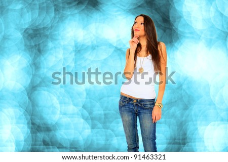 Stock photo of young, fit and sexy woman in jeans and white over bokeh blue background