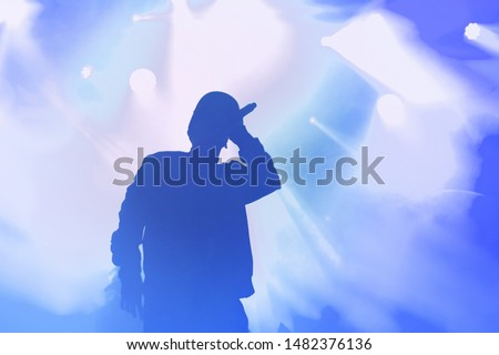 Stock photo of young rap singer with mic in hand singing popular song on stage in blue lights.Hip hop artist performing live on scene in music hall.Repper with microphone in royalty free backgrounds