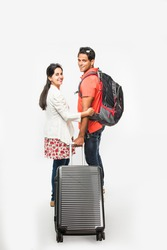 stock photo showing back of smart Asian or Indian couple traveler with suitcase and hike bag isolated over white background, going abroad or within country, perfect shot for tours and travels company
