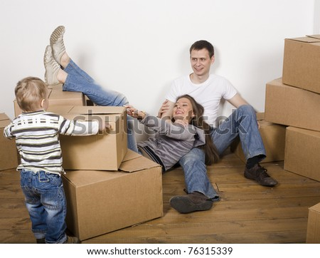 stock-photo-smiling-family-in-new-house-playing-with-boxes