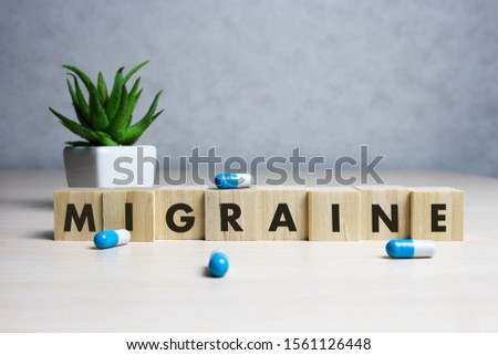Stock photo The word Migraine along with paracetamol tablets