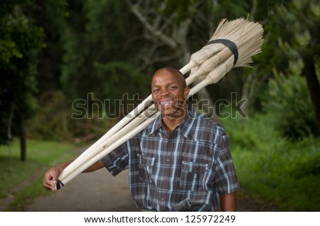 Stock photograph of a smiling black South African entrepreneur small business broom salesman in Hilton, Pietermaritzburg, Kwazulu-Natal