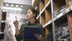 stock taking concept. low angle of beautiful young woman worker of furniture store standing in rows of shelves in stockroom. Asian manager woman doing stocktaking of products in parcels in warehouse