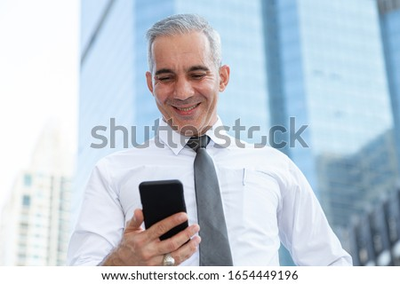 stock trader, investor, businessman happy after checking profit on investment portfolio from stock market on smartphone application at business office building center. business and financial concepts. Stock photo ©