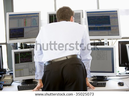 Stock Trader Looking At Multiple Monitors