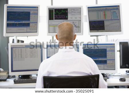 Stock Trader Looking At Multiple Monitors - stock photo