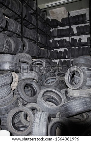 Stocked car tires and used tires stacked in a workshop hall