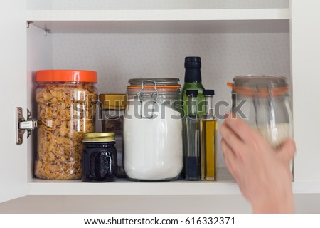stocked kitchen pantry with food - jars and containers of cereals, jam, coffee, sugar, flour, oil, vinegar, rice