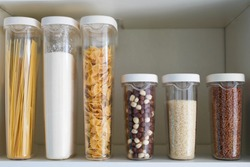 Stocked kitchen pantry with food - pasta, buckwheat, rice and sugar . The organization and storage in kitchen of a case with grain in plastic containers.