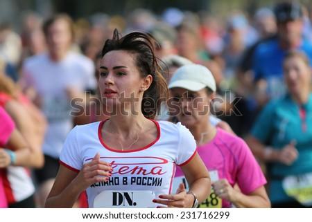 STOCKHOLM - SEPTEMBER 13, 2014: Young beautiful woman running in the Halvmarathon running event (21 km), Sept 13, 2014 in Stockholm, Sweden