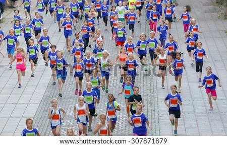 STOCKHOLM, SWEDEN - AUG 15, 2015: Large group of running girls and boys from above in the section for kids in the running event Midnattsloppet, August 15, 2015 in Stockholm, Sweden #307871879