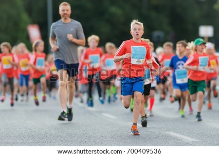 STOCKHOLM, SWEDEN - AUG 19, 2017: Midnight run or Midnattsloppet for kids at the streets of Stockholm. 2 km #700409536
