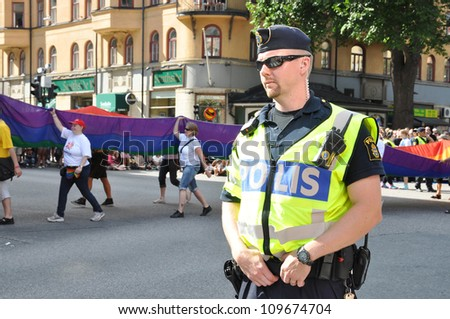 STOCKHOLM, SWEDEN - AUGUST 4: An unidentified policeman protects people taking part in Pride Parade 2012 to support gay rights on August 4, 2012 in Stockholm Sweden.