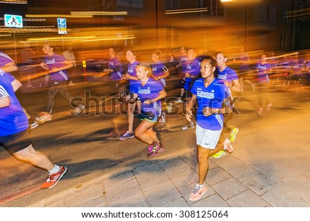 STOCKHOLM, SWEDEN - AUGUST 15, 2015: Female runners in colorful lights on the streets of Soder at Midnattsloppet or the Midnight run. The track is 10 km and goes thru the streets of Stockholm.