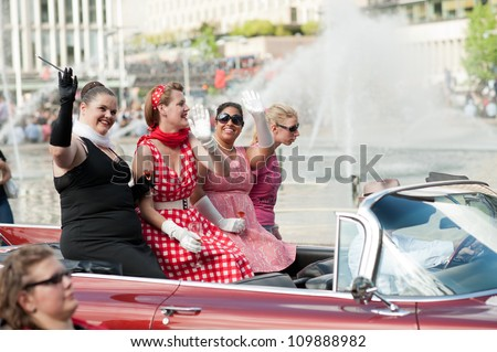 STOCKHOLM, SWEDEN - AUGUST 4: Four ladies ride a cabriolet at Stockholm Pride Parade on August 4, 2012 in Stockholm which attracts an estimated 50000 participants and 500000 spectators.
