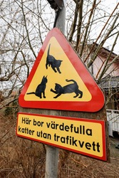 Stockholm, Sweden March 9, 2021 A beware of cats triangular sign in a neighborhood, and a sign saying in Swedish:
