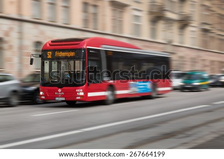 Stockholm, Sweden - March 31, 2015: Classic red buses in the public transportation system in the city of Stockholm with motion blur.
