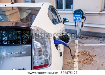 Stockholm, Sweden - October 10, 2015: Toyota Prius charge port, connector and cable at Stockholm city centr. Close up of the power supply plugged into an electric car being charged.
