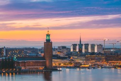 Stockholm, Sweden. Scenic Skyline View Of Famous Tower Of Stockholm City Hall And St. Clara Or Saint Klara Church. Popular Destination Scenic View In Sunset Twilight Dusk Lights. Evening Lighting.