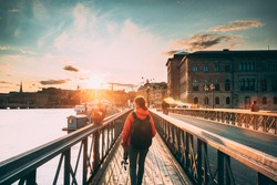 Stockholm, Sweden. Young Caucasian Woman Lady Tourist Traveler Walking On Famous Skeppsholmsbron - Skeppsholm Bridge. Popular Place, Landmark  And Destination In Stockholm, Sweden.
