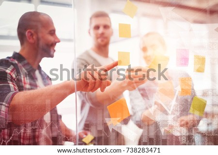 Stocks and shares against business people sticking adhesive notes in office #738283471