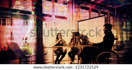 Stocks and shares against coworker on wheelchair with photo editors in meeting room