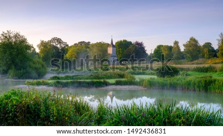 Stoke Charity, UK - Aug 21, 2019:  Dawn light and mist on the old mill pond in the village of Stoke Charity with the church of St Michael's in the distance Stock fotó ©