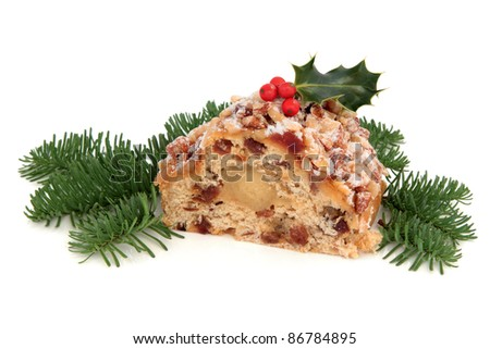 Stollen christmas cake with holly berry and blue pine fir leaf sprigs isolated over white background.