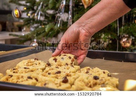 Stollen confectionery is placed on a baking sheet by someone. Concept: Christmas and baking