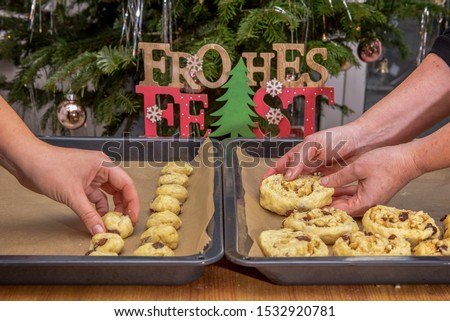 Stollen confectionery is placed on a baking sheet by someone. On a wooden sign is written in german (Frohes Fest). Concept: Christmas and baking