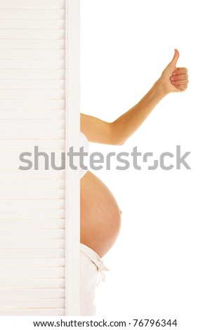 stomach and hand pregnant woman looked out from behind the door isolated on white